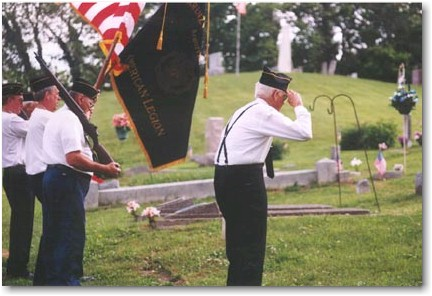 As Taps plays, the veterans bow their heads and salute